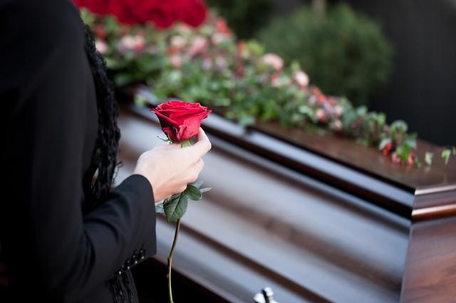 Mulher segurando rosa próxima do caixão